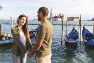 Italy, Venice, affectionate young couple with gondola boats in background - WPEF01250