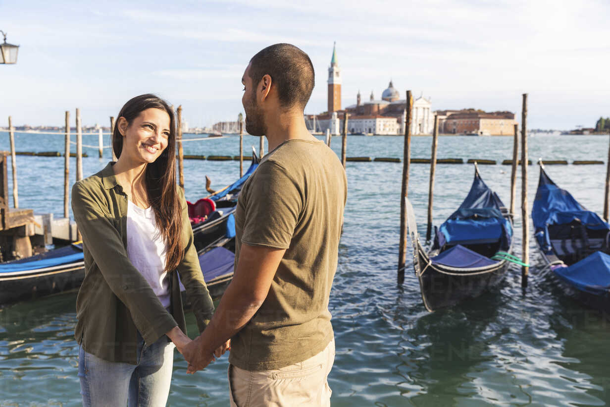 Italy, Venice, affectionate young couple with gondola boats in background - WPEF01250 - William Perugini/Westend61