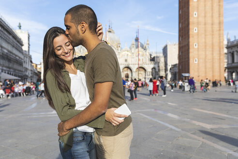 Italy, Venice, happy tourist couple kissing on St Mark's Square - WPEF01256