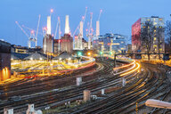 United Kingdom, England, London, view of railtracks and trains in the evening, former Battersea Power Station and cranes in the background - WPEF01264