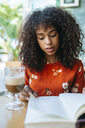 Portrait of young woman in a coffee shop reading a book - KIJF02137