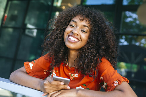 Portrait of laughing young woman with smartphone leaning on window sill of a coffee shop - KIJF02149