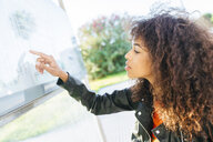 Young woman looking at schedule at bus stop - KIJF02155
