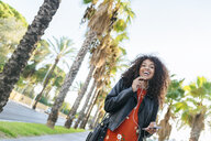 Portrait of laughing young woman with earphones on a promenade talking on mobile phone - KIJF02158