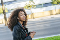 Portrait of smiling young woman listening music with earphones and smartphone - KIJF02161