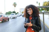 Portrait of smiling young woman with smartphone standing at roadside - KIJF02167