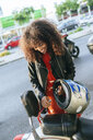 Smiling young woman removing safety lock from her motorcycle - KIJF02170
