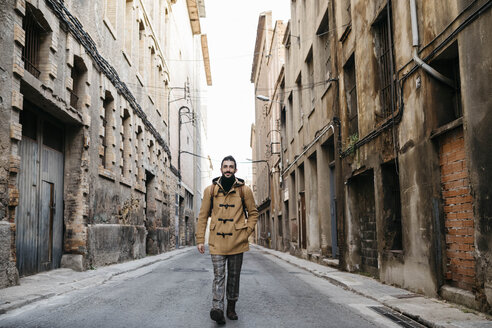 Spain, Igualada, man walking through the industrial zone of the town - JRFF02281