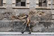 Spain, Igualada, man walking through the industrial zone of the town - JRFF02284