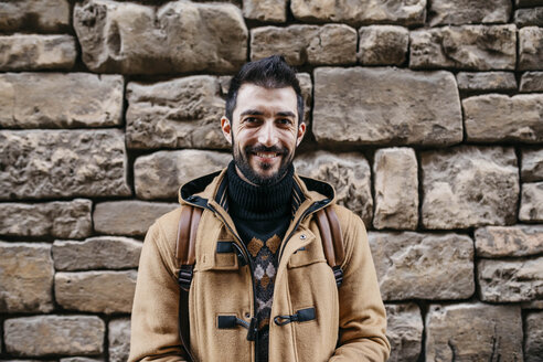 Spain, Igualada, portrait of smiling man at stone wall - JRFF02287