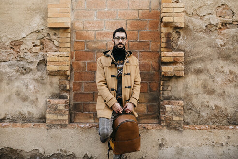Spain, Igualada, portrait of man with backpack standing at rundown building - JRFF02293