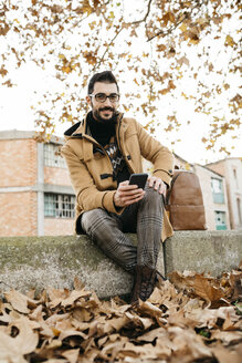 Spain, Igualada, portrait of smiling man with cell phone sitting down in the autumnal town - JRFF02296