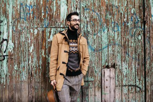 Spain, Igualada, smiling man standing at rundown wooden gate - JRFF02302