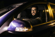 Portrait of confident man driving car at night - JRFF02320