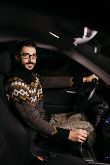 Portrait of confident man driving car at night - JRFF02326