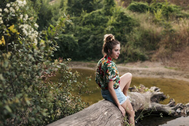 Young woman surrounded sitting on a trunk surrounded by nature. Barcelona, Catalonia, Spain. - LOTF00022