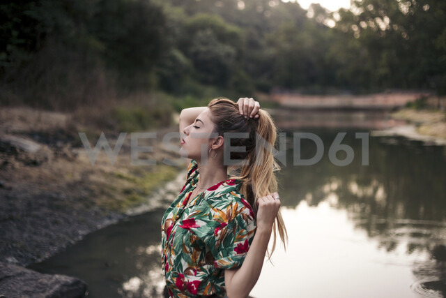 Young woman touching her hair next to a lake - LOTF00028 - Lucas Ottone/Westend61