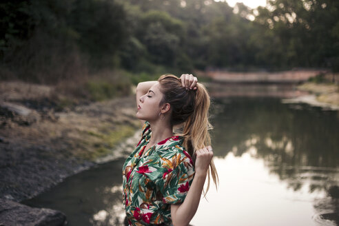 Young woman touching her hair next to a lake - LOTF00028