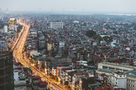 Vietnam, Hanoi, panoramic view of the city at dusk, with illuminated main road and dark residential areas - WPEF01275