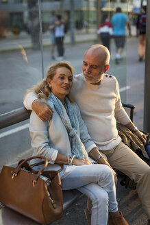 Spain, Barcelona, senior couple with baggage sitting at tram stop in the city - MAUF02239