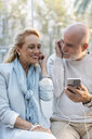 Spain, Barcelona, happy senior couple sharing smartphone with earbuds - MAUF02242