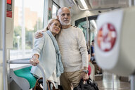 Affectionate senior couple standing in a tram - MAUF02245