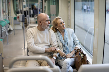 Senior couple sitting in a tram - MAUF02248
