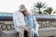 Spain, Barcelona, happy senior couple embracing on a bench - MAUF02251