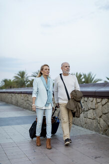Spain, Barcelona, senior couple walking with baggage on the promenade - MAUF02254