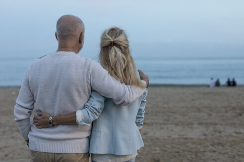 Spain, Barcelona, rear view of senior couple embracing on the beach at dusk - MAUF02257