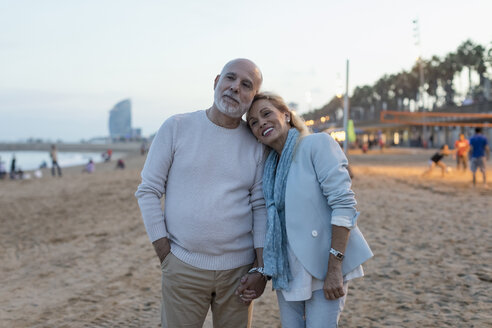 Spain, Barcelona, happy senior couple on the beach at dusk - MAUF02263