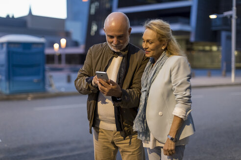 Spain, Barcelona, senior couple sharing cell phone in the city at dusk - MAUF02266