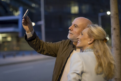 Spain, Barcelona, happy senior couple taking a selfie in the city at dusk - MAUF02269