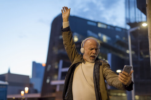 Spain, Barcelona, excited senior man with headphones and cell phone in the city at dusk - MAUF02272