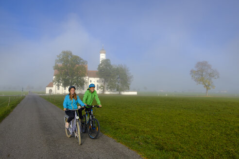 Germany, Pilgrimage Church St. Coloman and couple of cyclists on tour - LBF02332