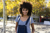 Portrait of a smiling woman, standing in a park - GIOF05301