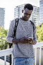 Young man standing on a bridge, using smartphone - GIOF05331