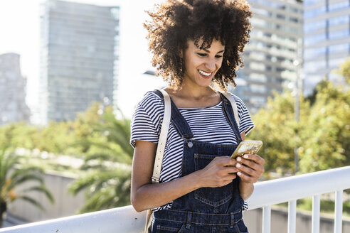 Young woman standing on a bridge, using smartphone - GIOF05334