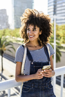 Young woman standing on a bridge, using smartphone - GIOF05337