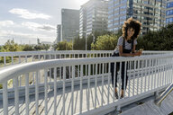 Young woman standing on a bridge, using smartphone, with headphones around her neck - GIOF05355
