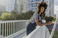 Young woman standing on a bridge, using smartphone, with headphones around her neck - GIOF05358