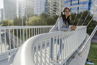Young woman standing on a bridge, listening music, using smartphone - GIOF05361