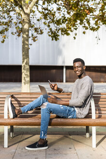 Young man sitting on a bench in the city, using laptop and smartphone - GIOF05388
