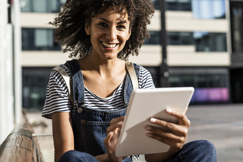 Mid adult woman with curly hair, sitting on a bench, using digital tablet - GIOF05394