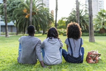 Three friends sitting in a park, watching the sunset - GIOF05430