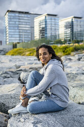 Young woman sitting on rocks at the beach, relaxing - GIOF05448
