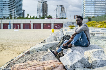 Young man sitting on rocks at the beach, relaxing - GIOF05451