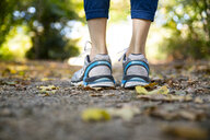 Close-up of spotive woman standing on autumnal footpath - CHPF00527