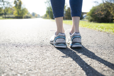 Close-up of spotive woman standing on footpath - CHPF00530