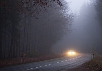 Car on country road in fog - WWF04754